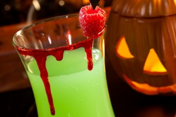 Closeup of Vampire's Kiss Cocktail, rum, melon liqueur, soda and touch of tabasco, garnished with fresh raspberry - Halloween drinks series